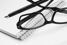 Eyeglasses and pen, on notepad Stock Photos
