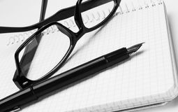 Eyeglasses and pen, on notepad Stock Photo