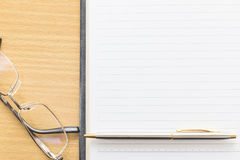 Eyeglasses and Pen on notepad with blank page Royalty Free Stock Photography