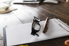 eyeglasses, pen and notepad on office desk Royalty Free Stock Photography
