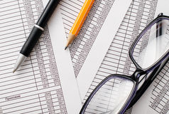 Eyeglasses, Pen and Pencil on Business Reports Royalty Free Stock Images
