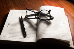 Eyeglasses and pen on plan book. Royalty Free Stock Photos