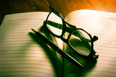 Eyeglasses and pen on plan book. Royalty Free Stock Images