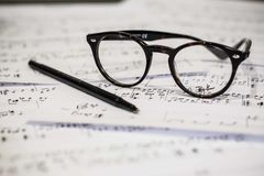 Eyeglasses and pen on sheet music Royalty Free Stock Photo