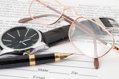 Eyeglasses and pen and wristwatch Stock Image