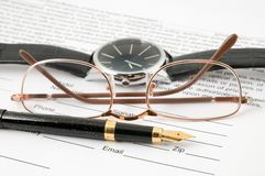 Eyeglasses and pen and wristwatch Royalty Free Stock Images