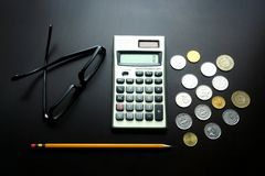 Eyeglasses, pencil, calculator and coins on a wooden table Royalty Free Stock Images
