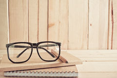 Eyeglasses , pencil and notebook on wooden table Royalty Free Stock Photos