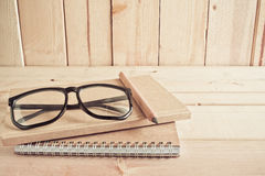 Eyeglasses , pencil and notebook on wooden table Stock Photos