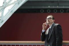 Eyeglasses Pensive Businessman talking on phone Stock Images