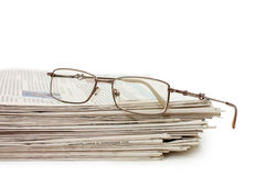 Eyeglasses on a pile of newspapers royalty free stock photos