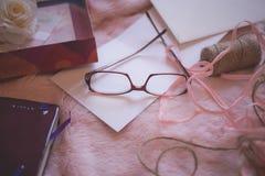Eyeglasses Beside Pink Yarn on Pink Bed Blanket Royalty Free Stock Photos