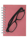 Eyeglasses place on red notebook on white background. Stock Image
