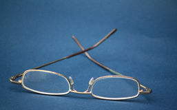 Eyeglasses in plain blue background Stock Photo