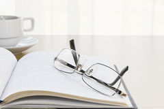 Eyeglasses put on a book with on the desk Royalty Free Stock Photos