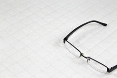 Eyeglasses put on white patchwork Quilt Royalty Free Stock Photo