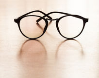 Eyeglasses with reflection on wooden table Royalty Free Stock Images