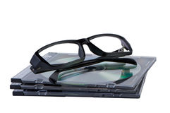 Eyeglasses on stack of CD DVD discs. Royalty Free Stock Image