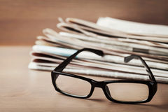 Eyeglasses and stack of newspapers on wooden desk for themes of ophthalmology, poor vision and reading Stock Image