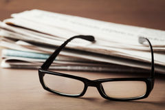 Eyeglasses and stack of newspapers on wooden desk for themes of ophthalmology, poor vision and reading Stock Images