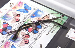 Eyeglasses on stamps Stock Photos