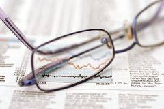 Eyeglasses on stock sheet Royalty Free Stock Image
