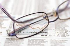 Eyeglasses on stock sheet Royalty Free Stock Image