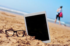 Eyeglasses and tablet with black blank space in the screen, in t Stock Photography