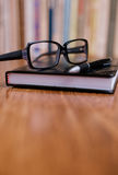 Eyeglasses on Top of the Book at the Table Stock Photos