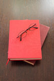 Eyeglasses and two red books Royalty Free Stock Photography