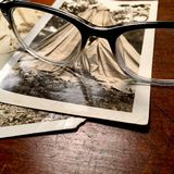 Eyeglasses with vintage photographs. Retro spectacles on a background of weathered black and white photographs royalty free stock photos