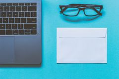 Eyeglasses, white paper envelope and laptop. Work space. Top vie. Eyeglasses, white paper envelope and laptop. Work space. Blue background. Top view Stock Image
