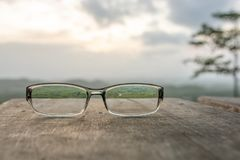 Eyeglasses on wooden table. And sunrise background Royalty Free Stock Images