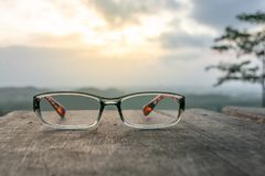 Eyeglasses on wooden table. And sunrise background Stock Image