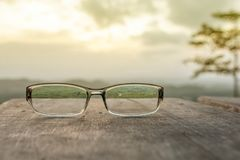 Eyeglasses on wooden table. And sunrise background Royalty Free Stock Photo