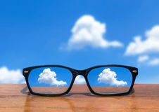 Eyeglasses on wooden table front of abstract white clouds Stock Photography