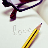Eyeglasses and word love in a notebook Royalty Free Stock Images
