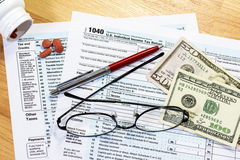 Eyeglasses on your tax forms needing filled out. Federal tax forms with asprin and money Royalty Free Stock Photography