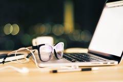 Eyeglasses z rozpieczętowanym laptopem i hełmofonami na drewnianym stole przy zdjęcia royalty free