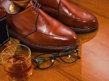 Eyeglassesand szkło whisky, nawoskuje Derby buty błyszczy luz obrazy stock