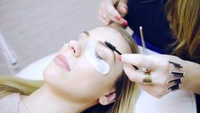 Eyelash extension procedure in beauty salon stock video
