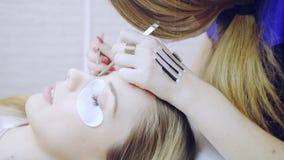Eyelash extension procedure in beauty salon stock footage