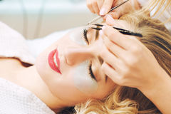 Eyelash extension procedure in beauty salon. Royalty Free Stock Images