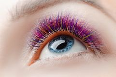Eyelash extension procedure. Beautiful woman with long colored hairs lash in beauty spa salon stock photography
