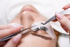 Eyelash Extension Procedure. Woman Eye with Long Eyelashes. Lashes, close up, selected focus. Eyelash Extension Procedure. Woman Eye with Long Eyelashes. Lashes Stock Images