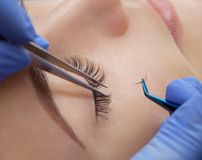 Eyelash removal procedure close up. Beautiful Woman with long lashes in a beauty salon. Eyelash extension Stock Photography
