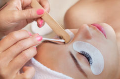 Eyelash removal procedure close up. Beautiful Woman with long lashes in a beauty salon. Eyelash extension Stock Photos