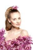 秀丽少妇,有兰花花的豪华长的卷发 理发 美丽的女孩新鲜的健康皮肤,构成,嘴唇, eyelashe 免版税图库摄影
