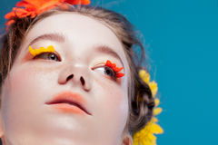 Eyelashes like petals of flowers. Beautiful young girl in the image of flora, close-up portrait royalty free stock photography