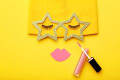 Eyelashes with paper lips, glasses and lip gloss. On yellow background. Minimalism concept stock photos